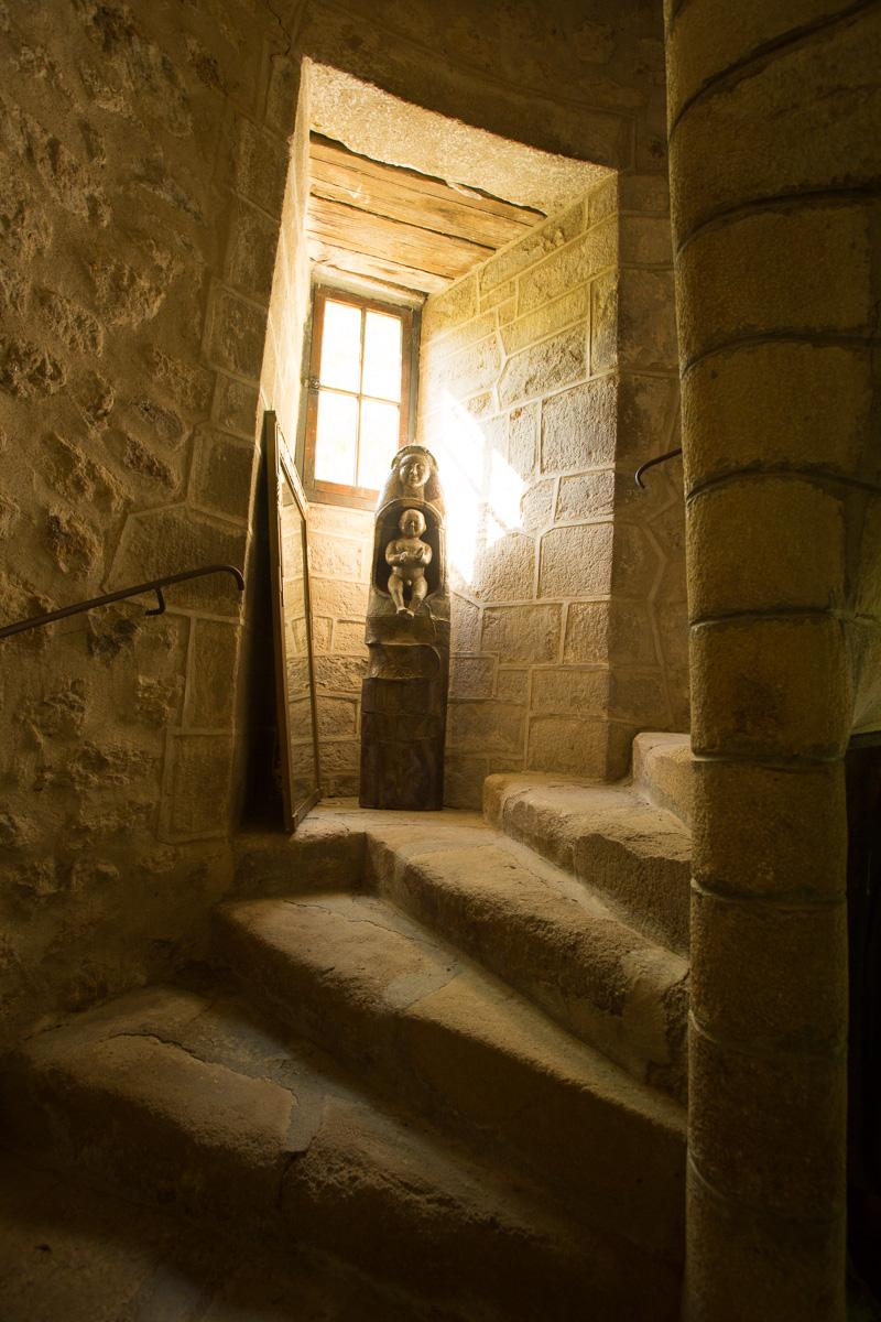 """Escalier à vis (16e siècle). Dans l'embrasure, """"Vierge à l'enfant"""", sculpture de Martine Diersé. Photo Simon Bugnon."""
